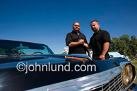 Two Hispanic Men Clasping Hands in a brotherhood fashion at a classic car show near Tracy California.  The men have short hair and are dressed in black.